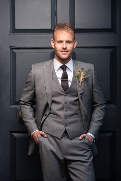 man in gray suit jacket and blue dress pants