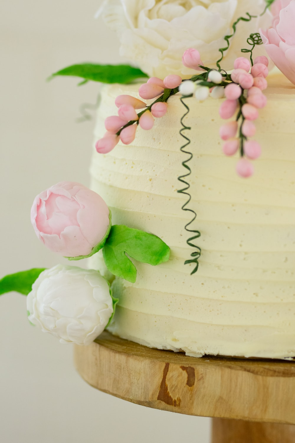white and green cake with pink flower on top