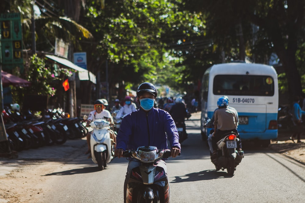 man in blue helmet riding on motorcycle during daytime