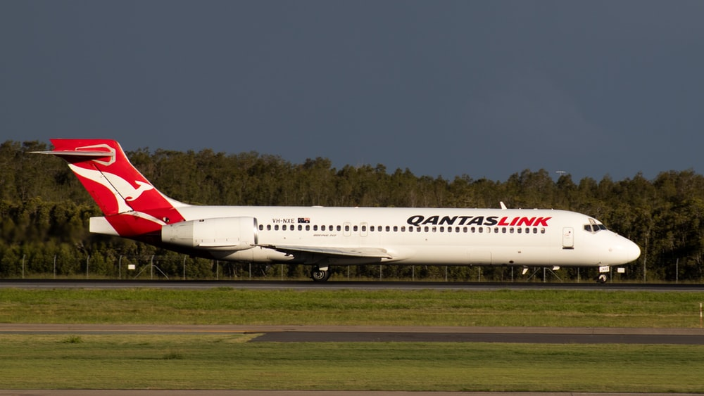 white and red passenger plane on green grass field under blue sky during daytime