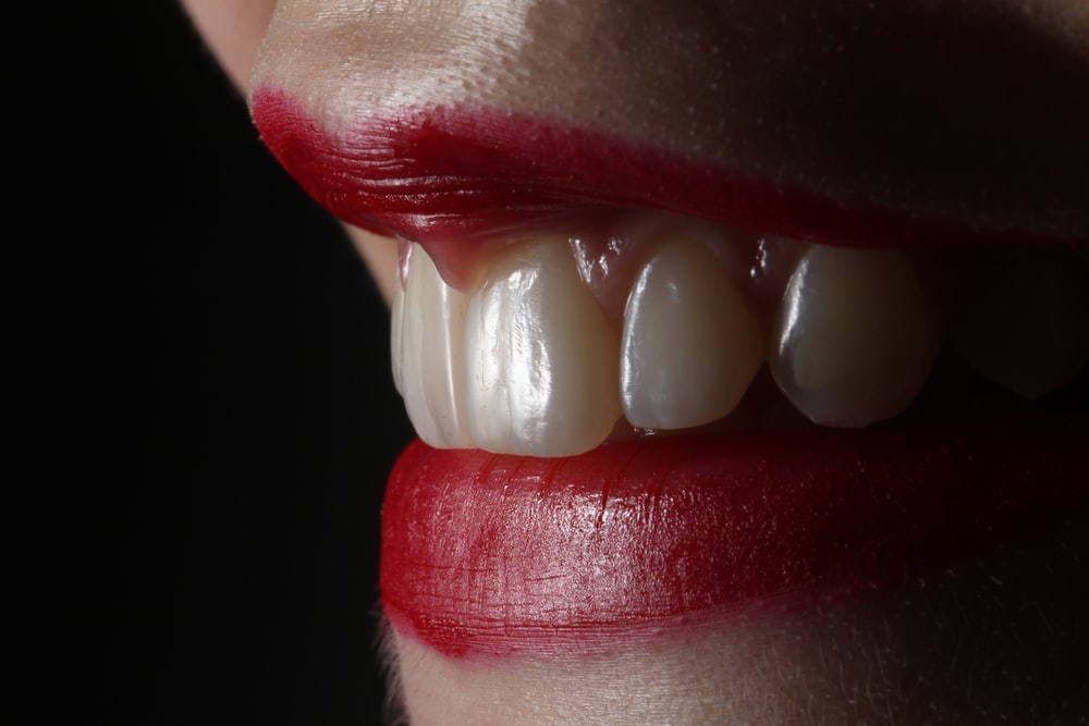person with red lipstick and white pearl earrings