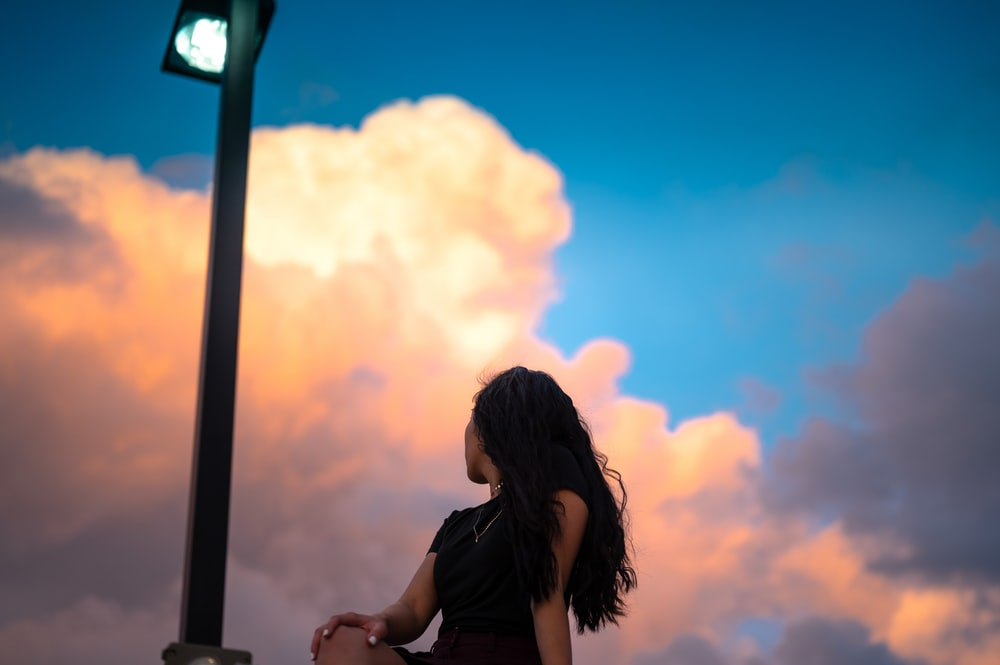 woman in black shirt standing and smiling during sunset