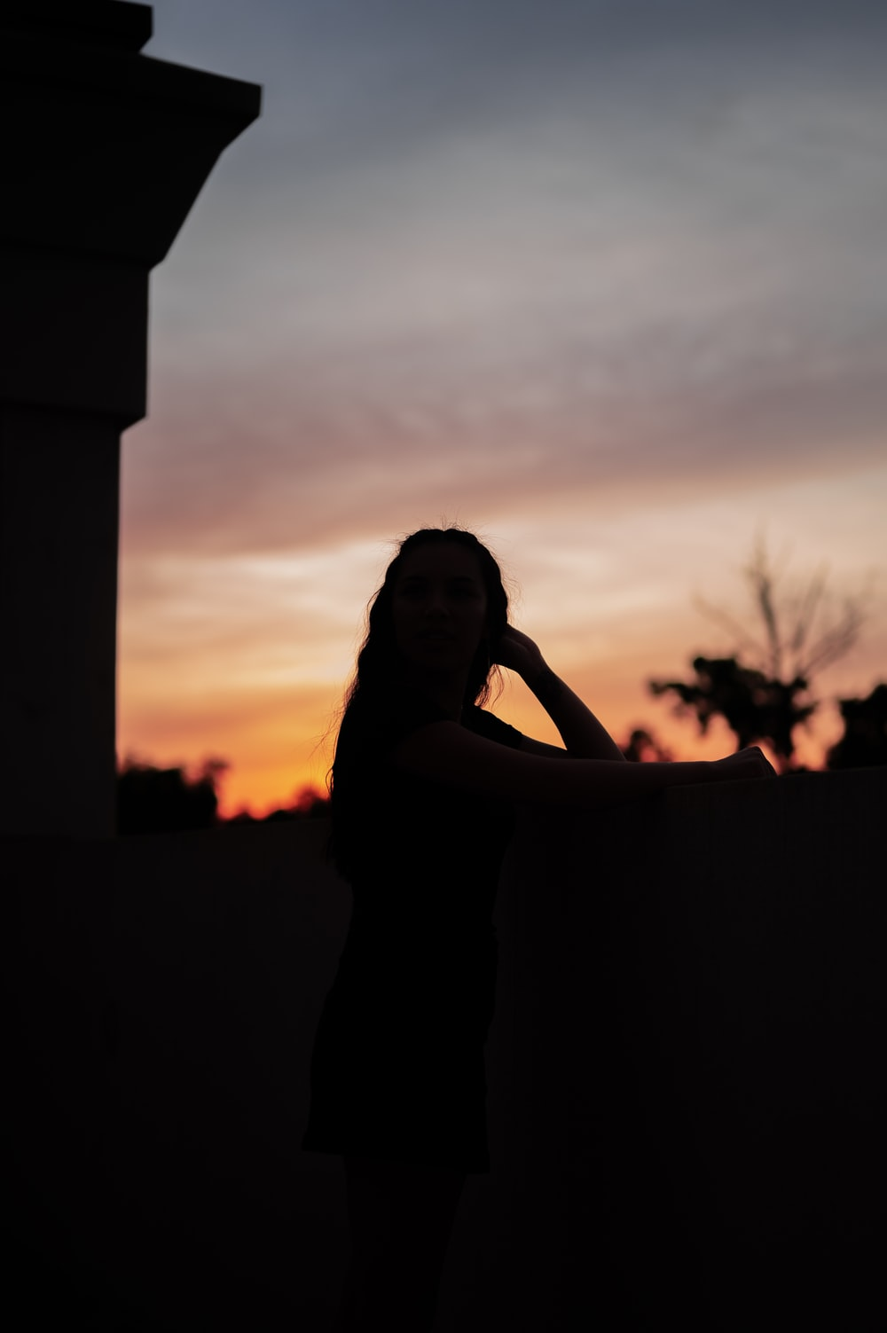 woman in black dress standing during sunset