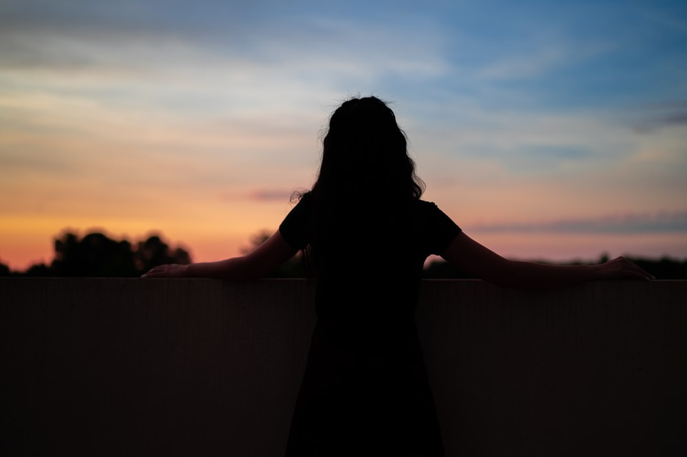 silhouette of woman standing on top of building during sunset
