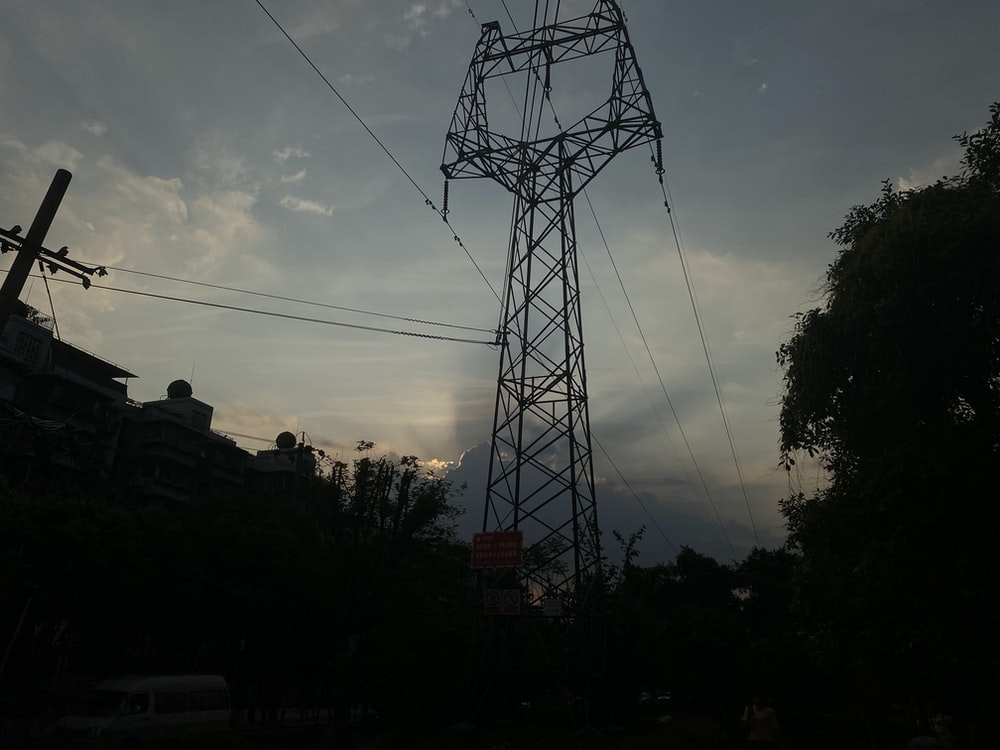 silhouette of electric tower during sunset