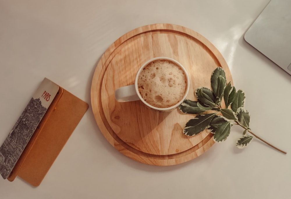 white ceramic mug on brown wooden round plate
