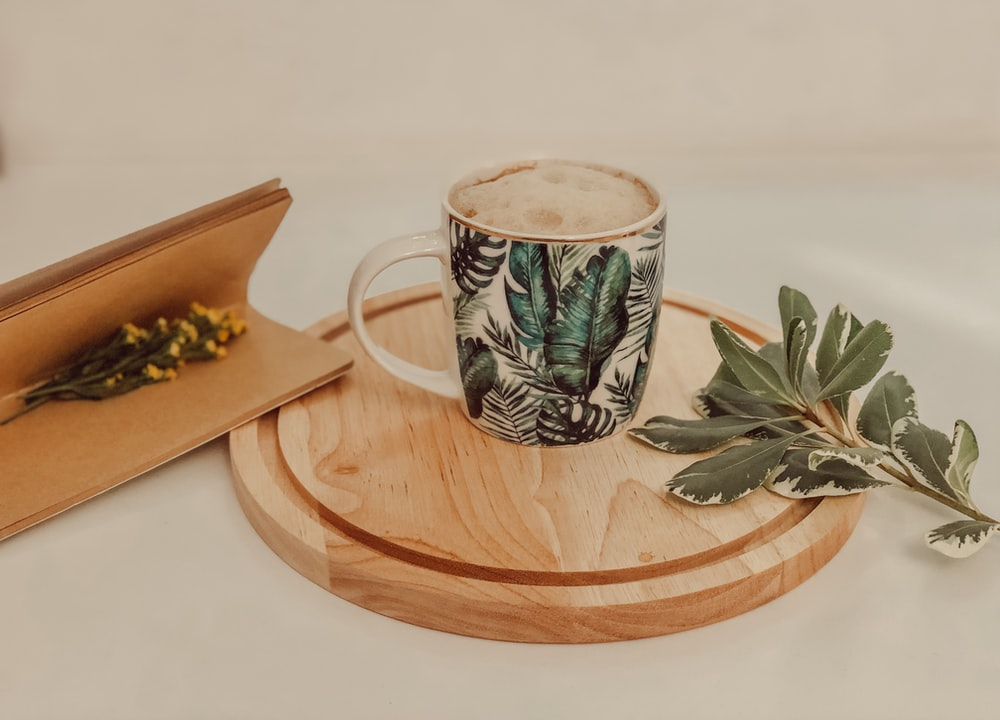 white and green floral ceramic mug on brown wooden coaster