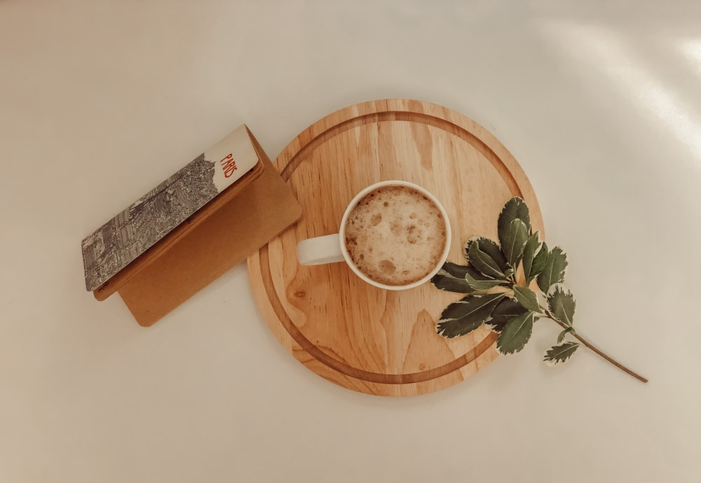white ceramic mug on brown wooden round tray
