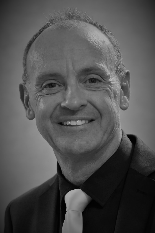 man in black suit smiling
