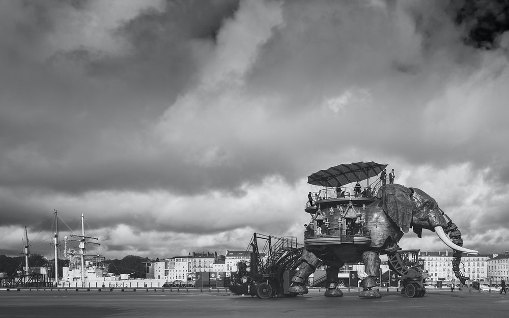 grayscale photo of people riding on horse carriage