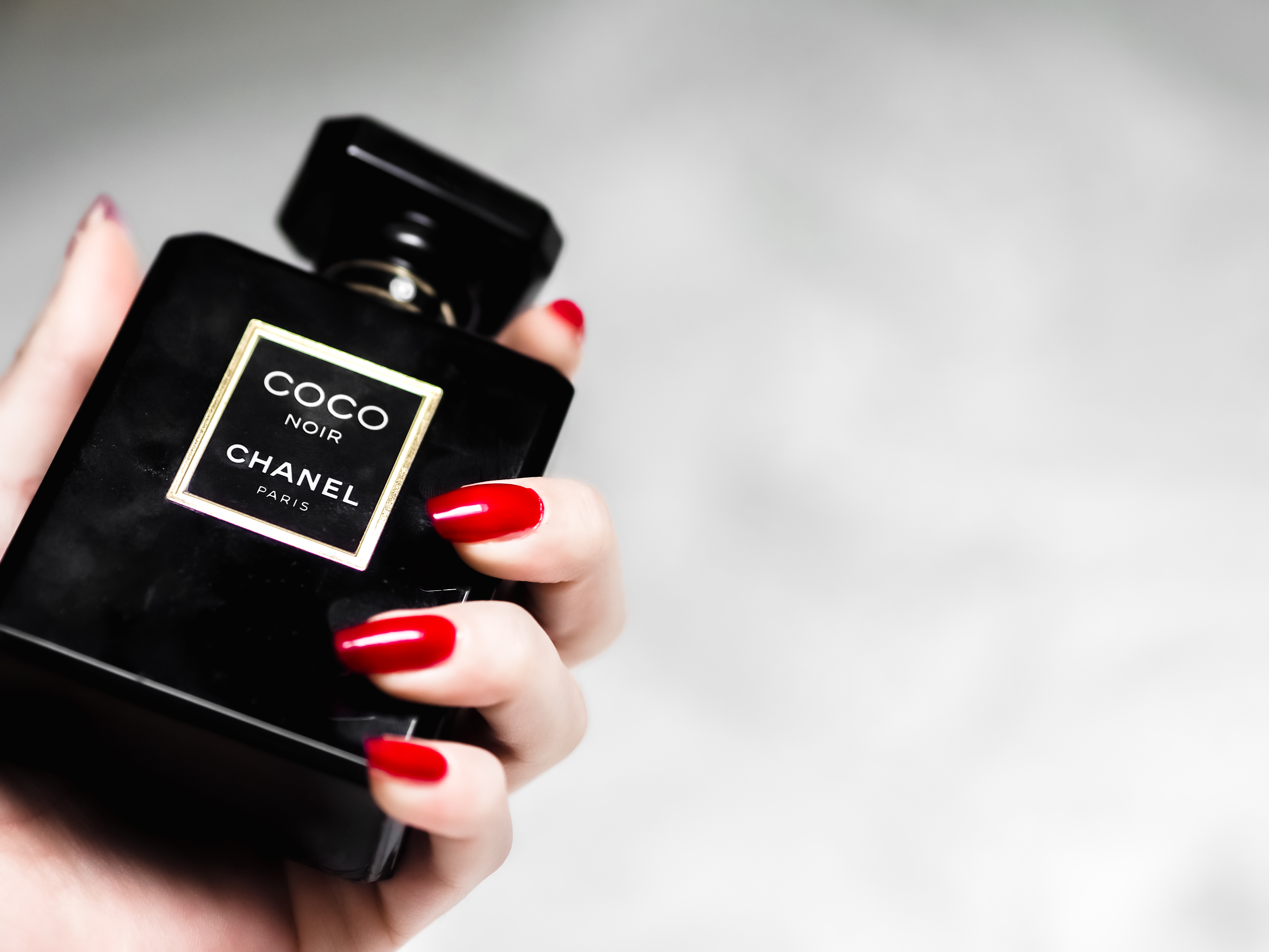 person holding black and gold perfume bottle