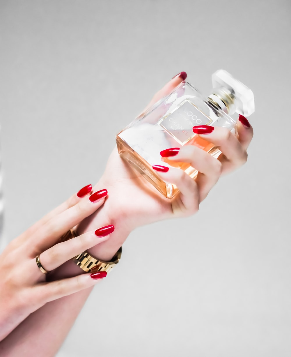 person holding clear glass bottle