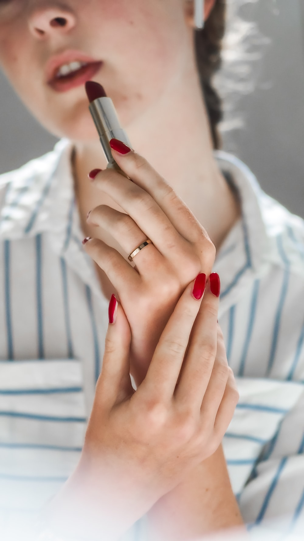 woman in red manicure and gold ring