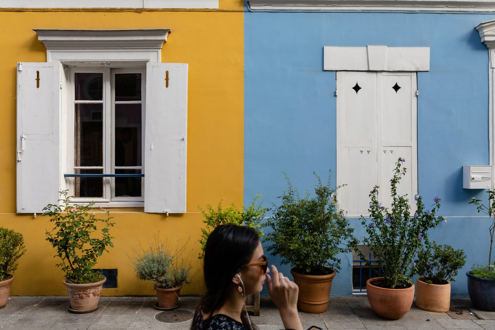 woman in black tank top sitting beside blue painted wall during daytime