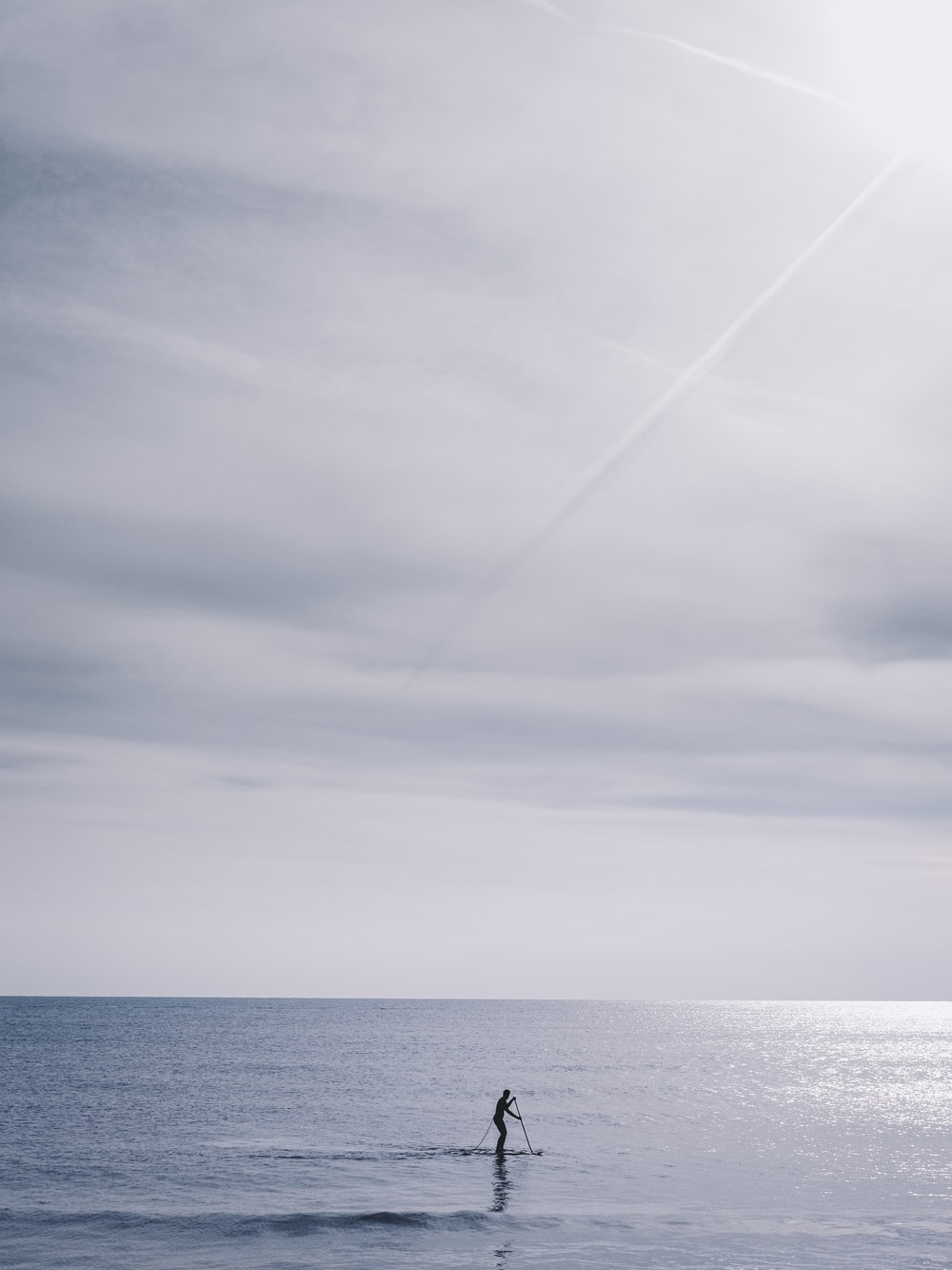 person in boat on sea under cloudy sky during daytime