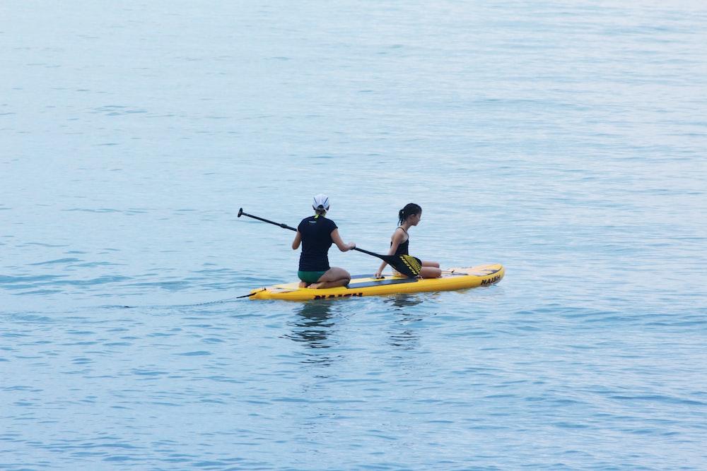 2 men riding yellow kayak on sea during daytime