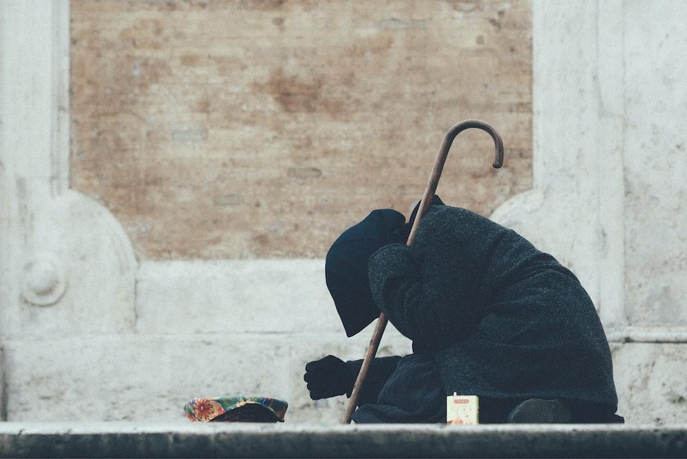 person in black jacket sitting on floor