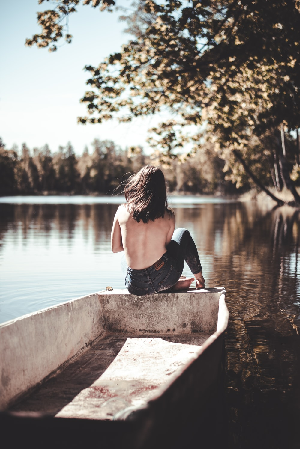 woman in black tank top sitting on concrete dock during daytime