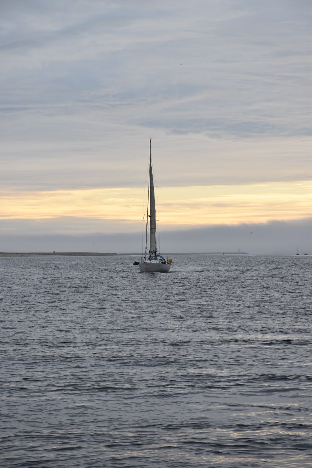 white sail boat on sea during sunset