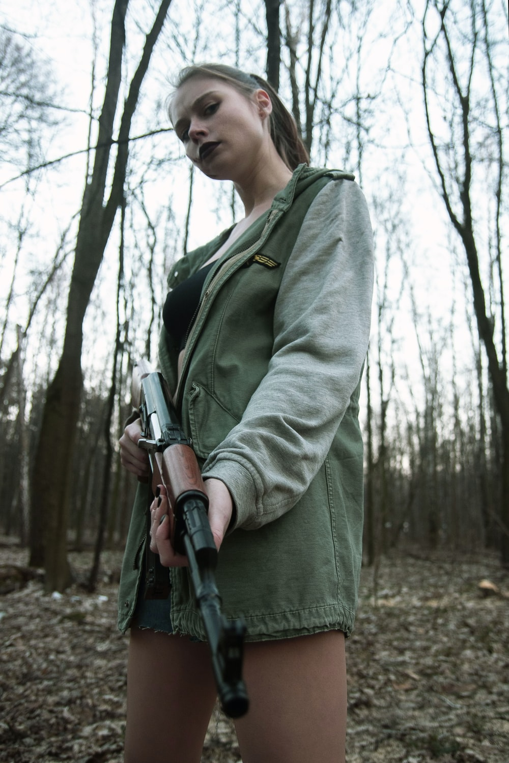 woman in green coat holding black rifle