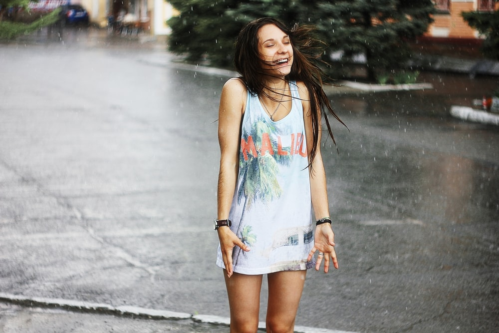 woman in white tank top and blue denim shorts standing on road during daytime