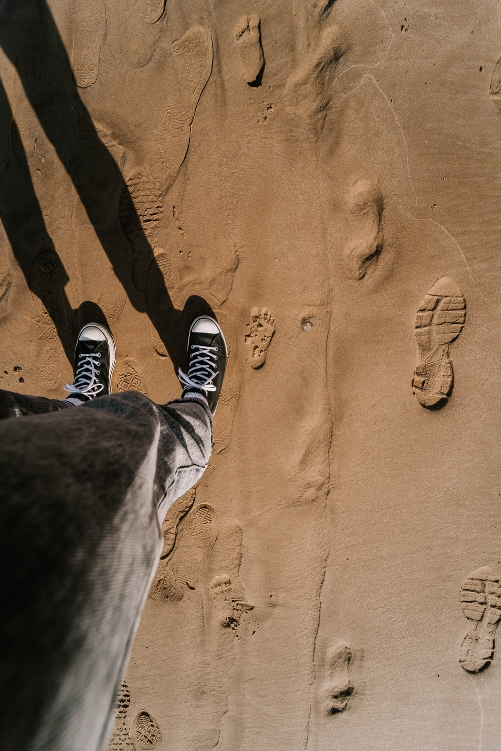 person in black pants and black and white sneakers standing on brown sand