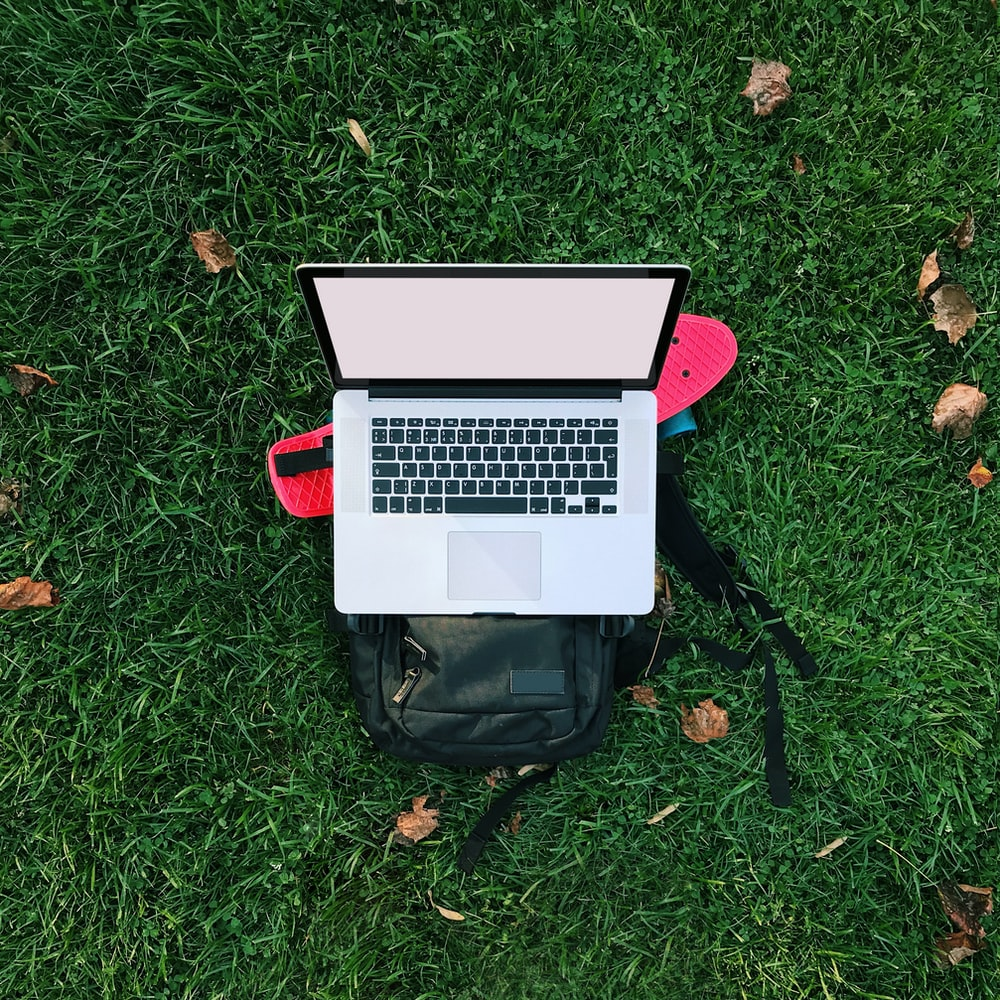 macbook air on black backpack on green grass