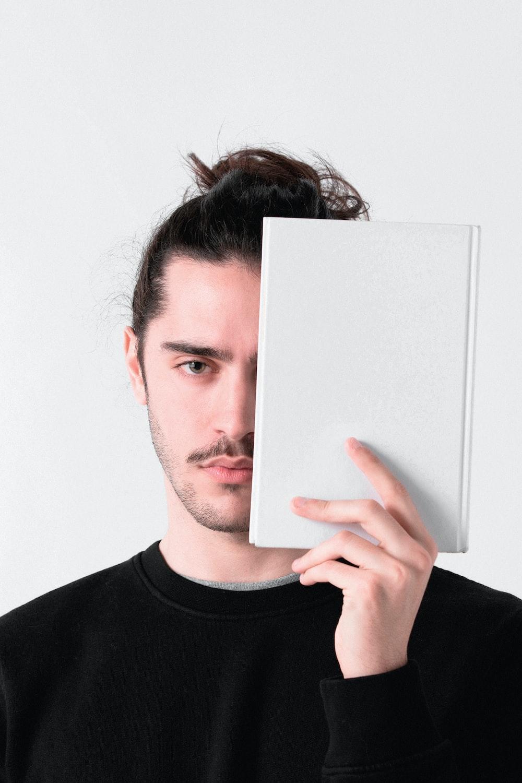 man in black crew neck shirt holding white paper