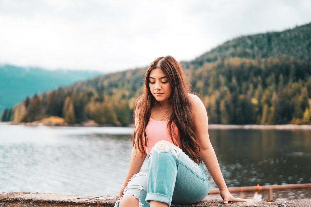 woman in blue denim jeans sitting on brown wooden dock during daytime