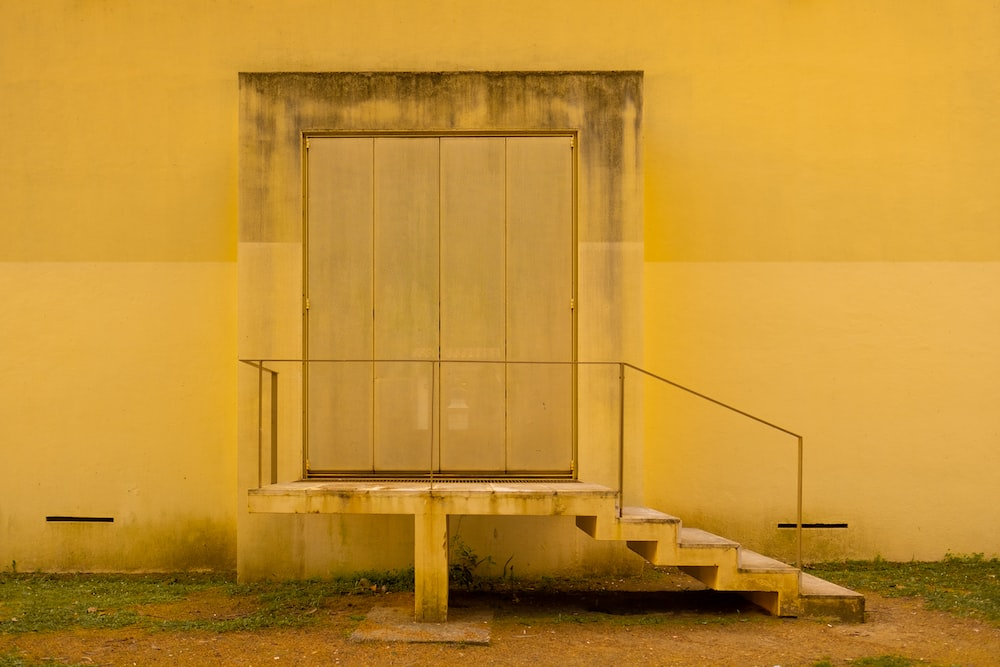 white concrete building with gray wooden door