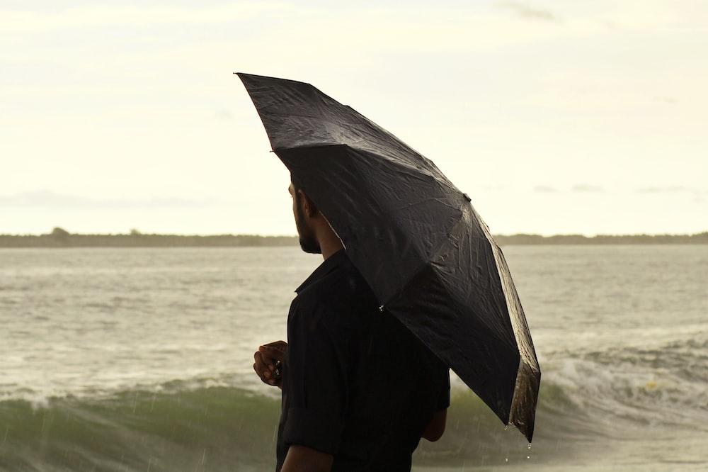 woman in black long sleeve shirt holding umbrella standing on seashore during daytime