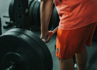 man in orange t-shirt and red shorts carrying black barbell