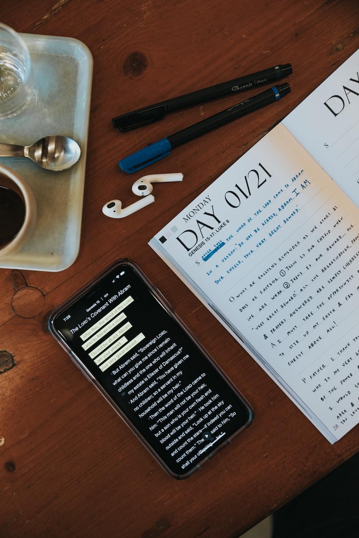 white printer paper beside black pen and white ceramic mug on brown wooden table