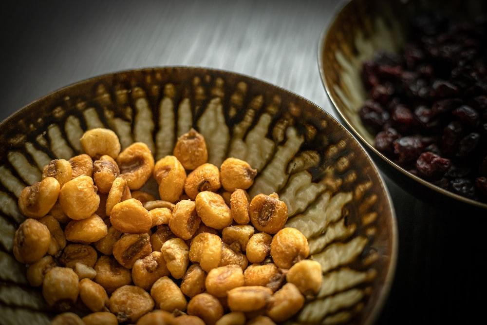 brown peanuts on black ceramic bowl