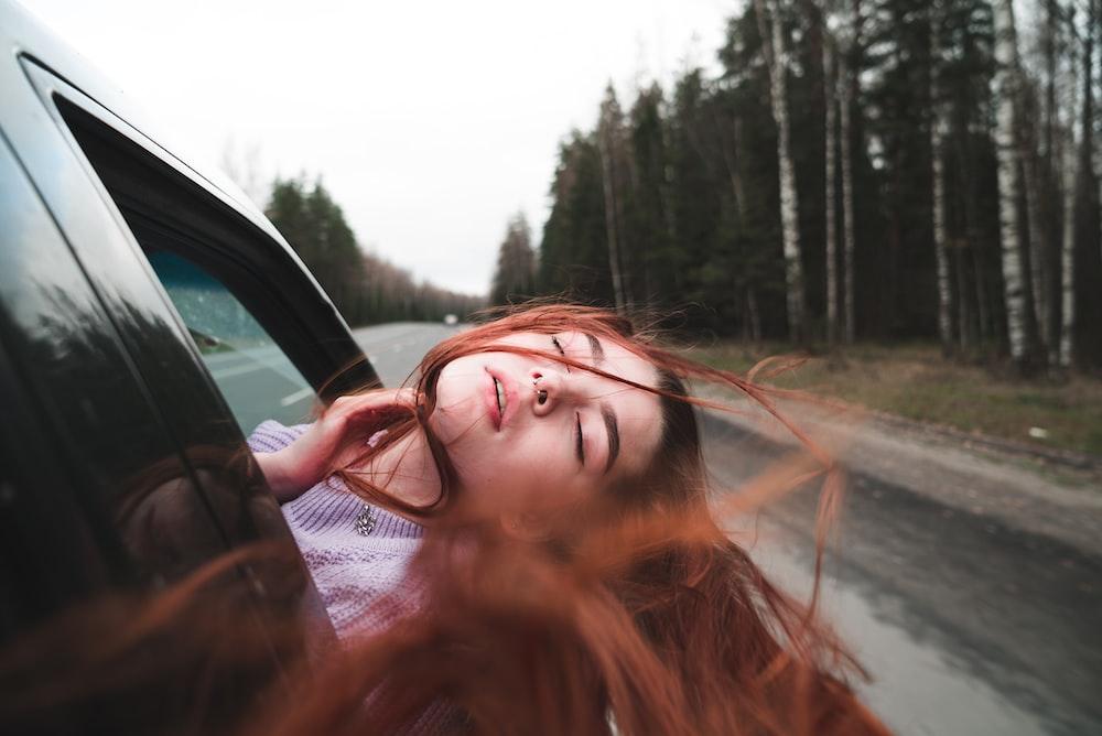 woman in black framed eyeglasses driving car during daytime