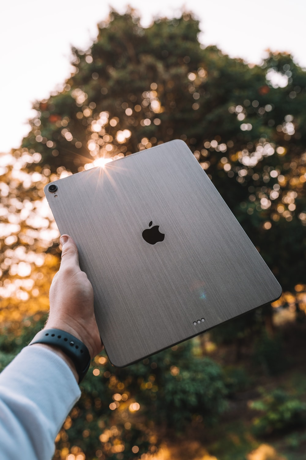 person holding silver apple macbook