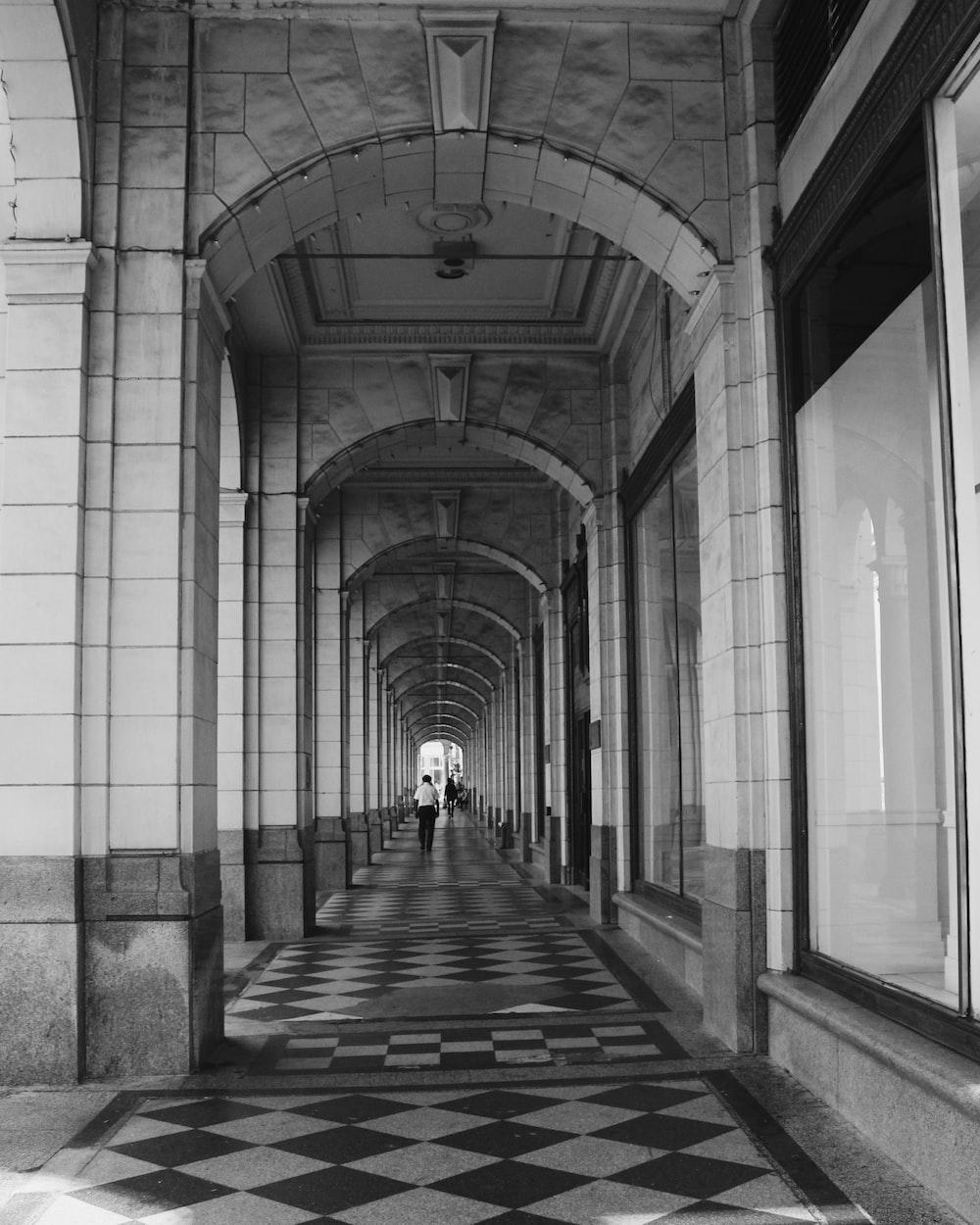 grayscale photo of hallway with glass windows