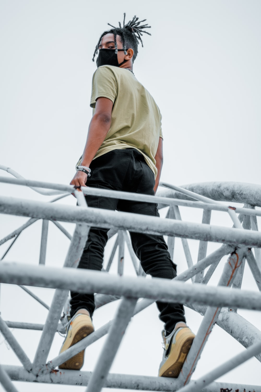 man in yellow shirt and black pants climbing on gray metal ladder during daytime