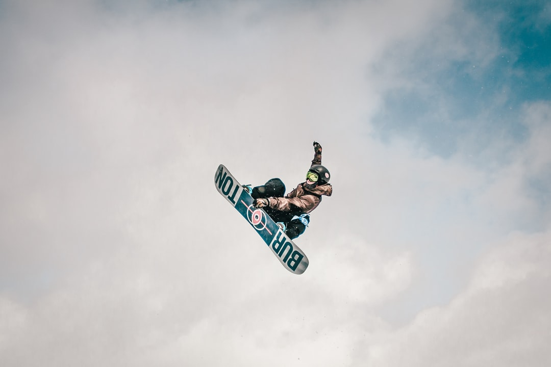 Man In Black Jacket and Blue Pants Riding On Snowboard Under White Clouds During Daytime - unsplash