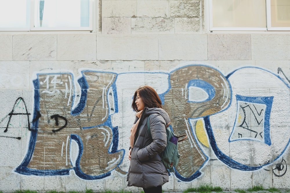 woman in gray jacket standing beside wall with graffiti during daytime