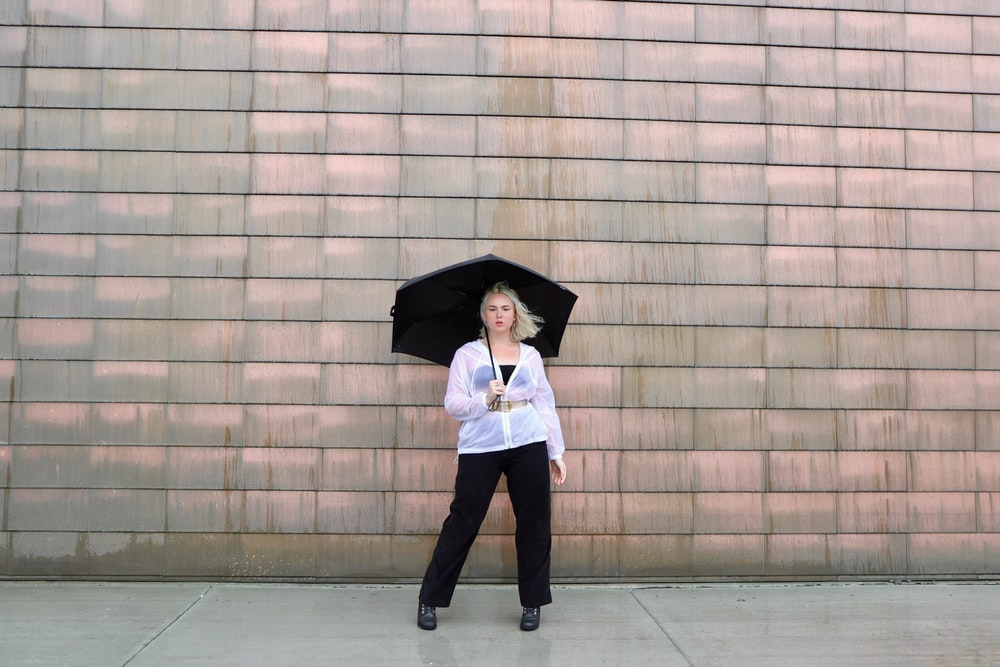 woman in white long sleeve shirt and black pants holding umbrella
