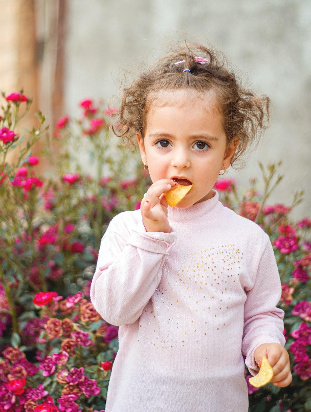 girl in white long sleeve shirt eating orange fruit