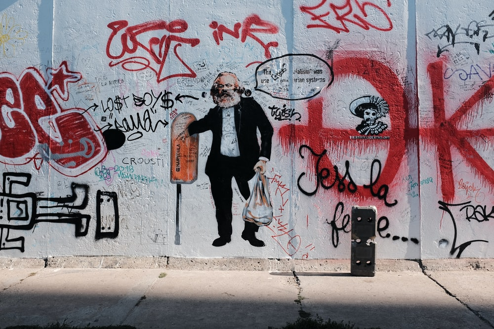 man in black jacket standing beside wall with graffiti during daytime