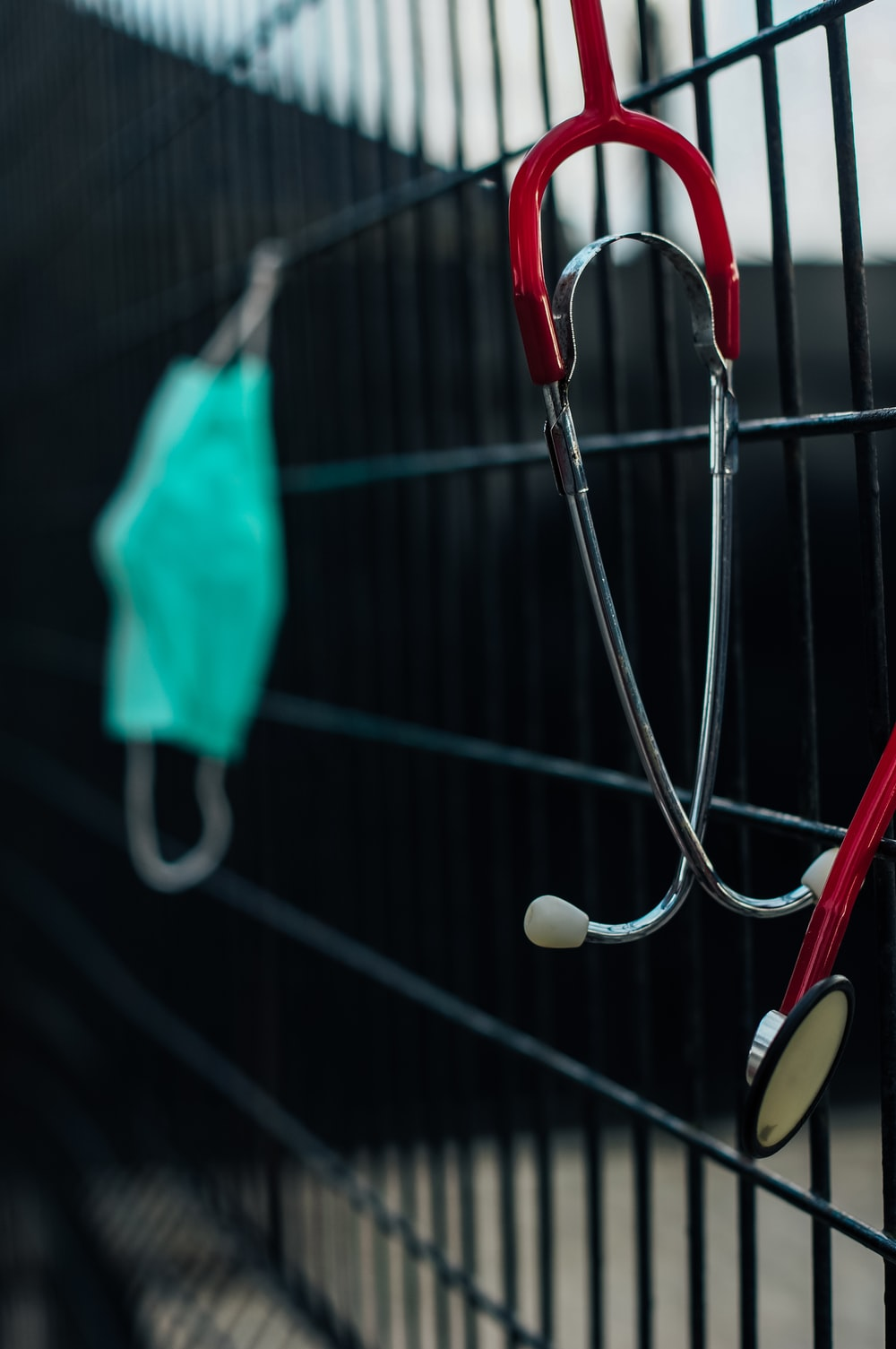 blue and white stethoscope hanging on black metal fence