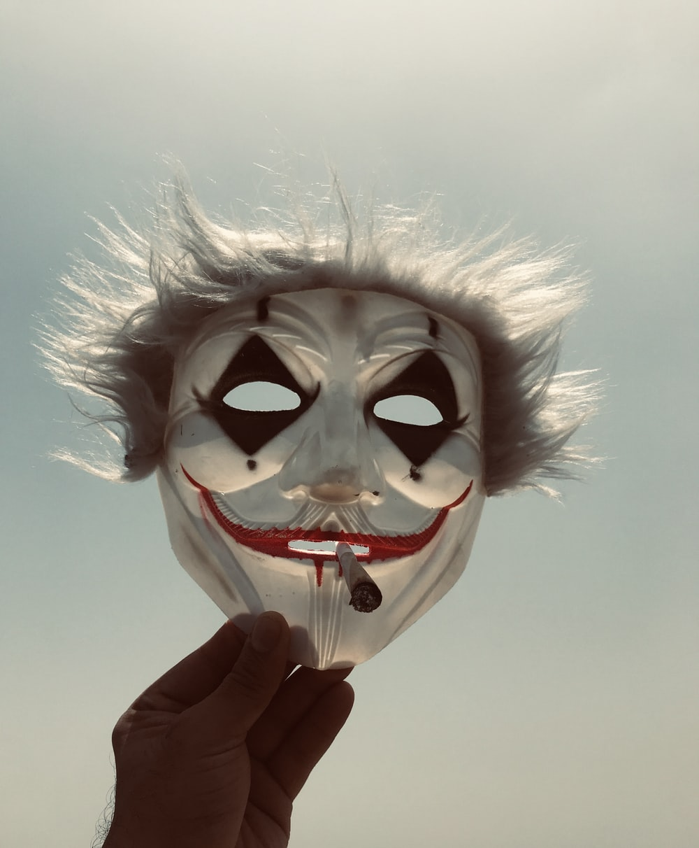 person holding white and red mask