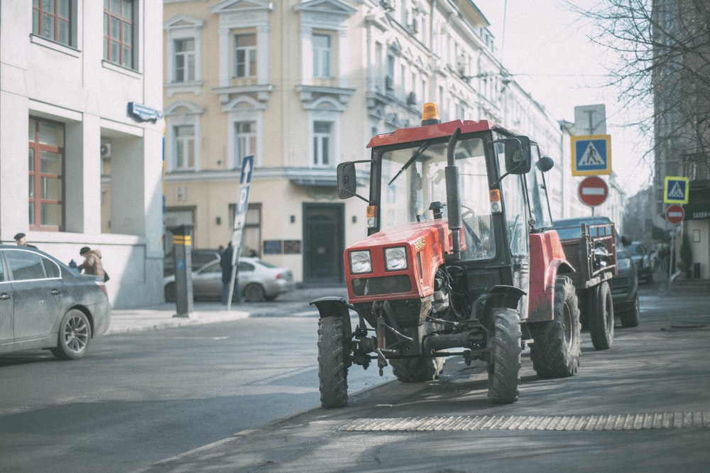 red and black tractor on road during daytime