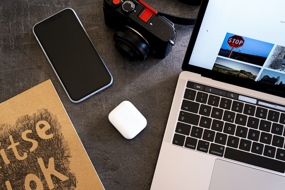 black and red dslr camera beside macbook pro