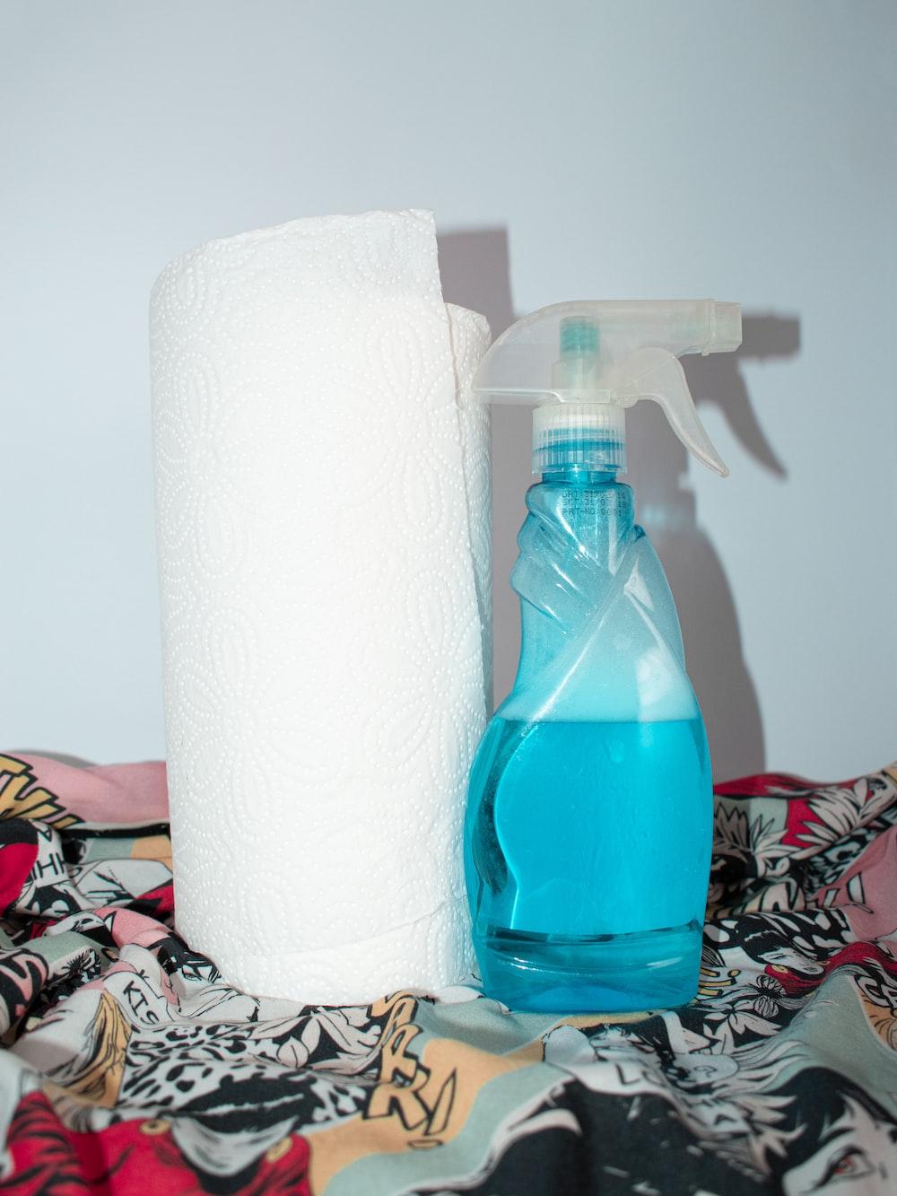 white tissue paper roll beside blue plastic bottle