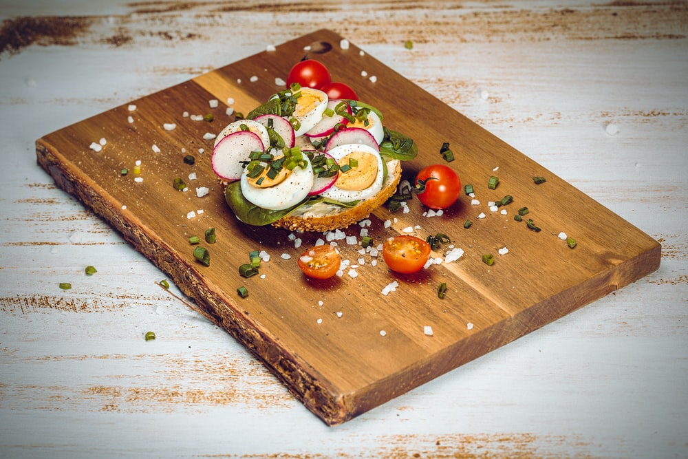 sliced cucumber and tomato on brown wooden chopping board