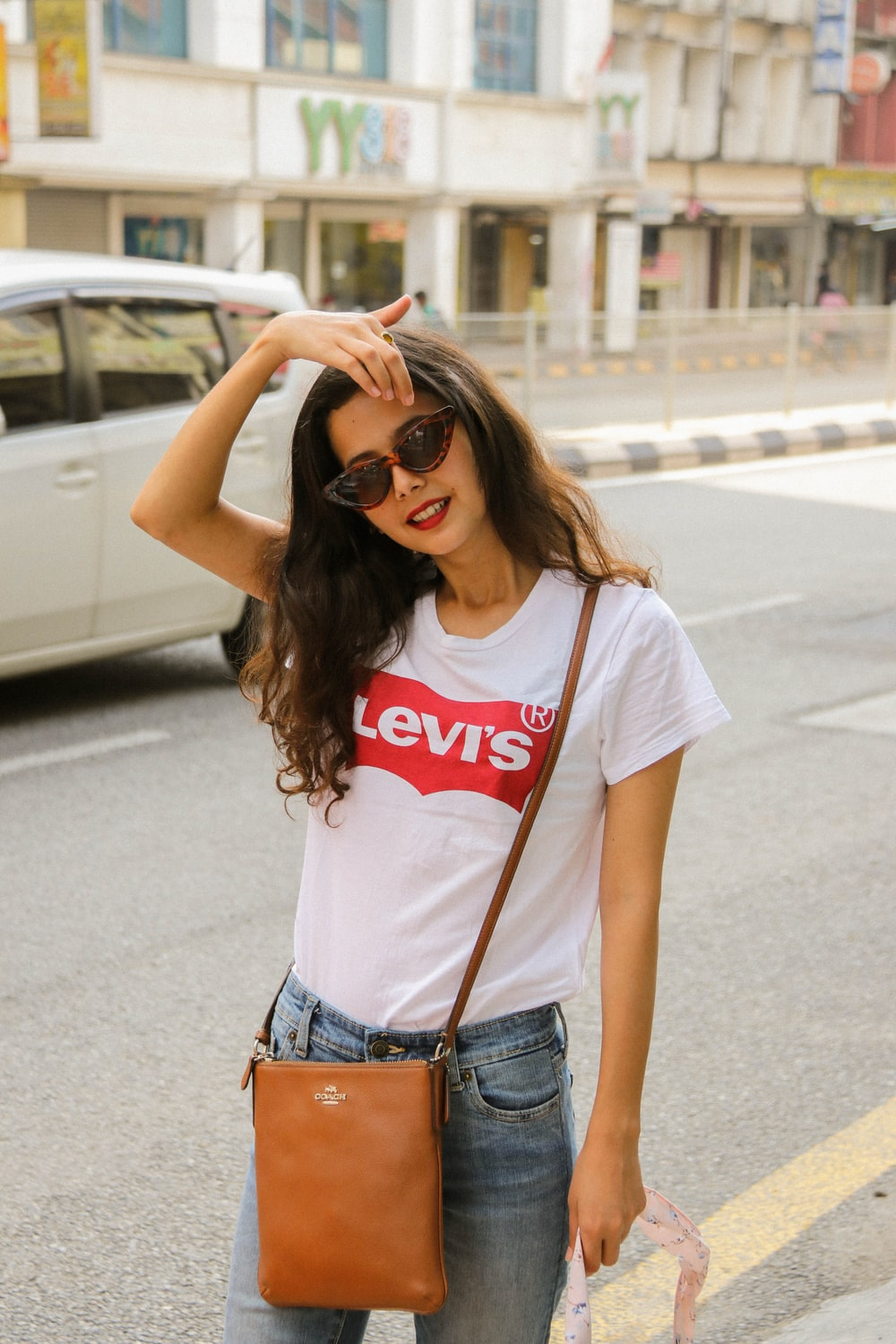 woman in white and red crew neck t-shirt and blue denim jeans standing on road